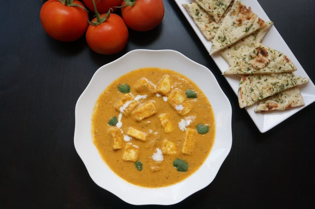 Instant Pot Paneer Butter Masala topped with cilantro and cream with naan bread on the side