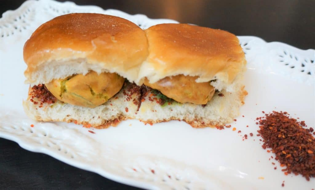 Vada Pav is the humble street food of Mumbai. A fried potato fritter in chickpea batter or vada, is stuffed in between mini-burger buns called pav, along with sweet and spicy sauces or chutney.
