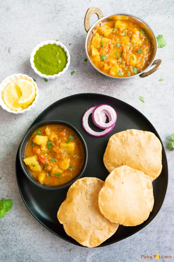Instant Pot Potato Curry in Tomato Sauce served with poori, green chutney and lemons