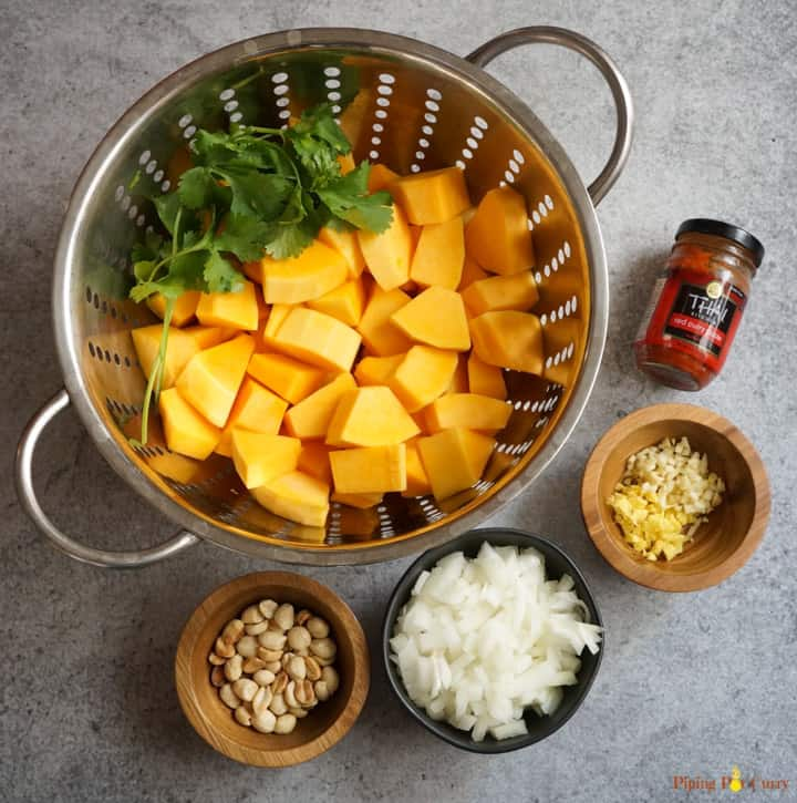 Instant Pot Vegan Thai Butternut Squash Soup Ingredients - squash cut in pieces, peanuts, onions, ginger, garlic and red curry paste