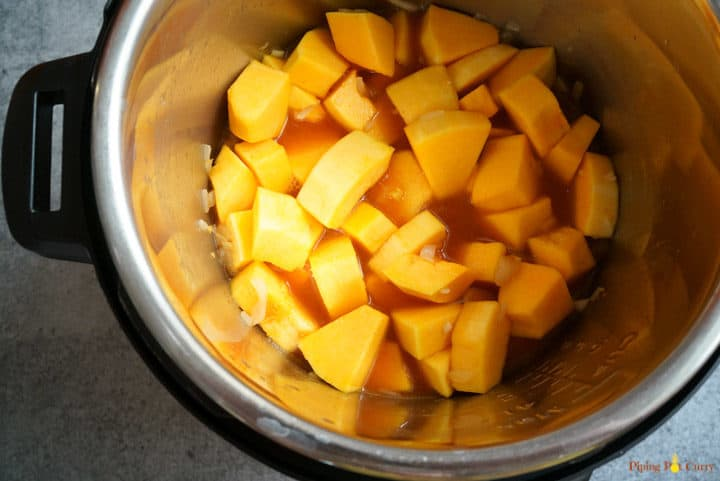 Instant Pot Vegan Thai Butternut Squash Soup - Step 2 add squash, red curry paste, salt and broth