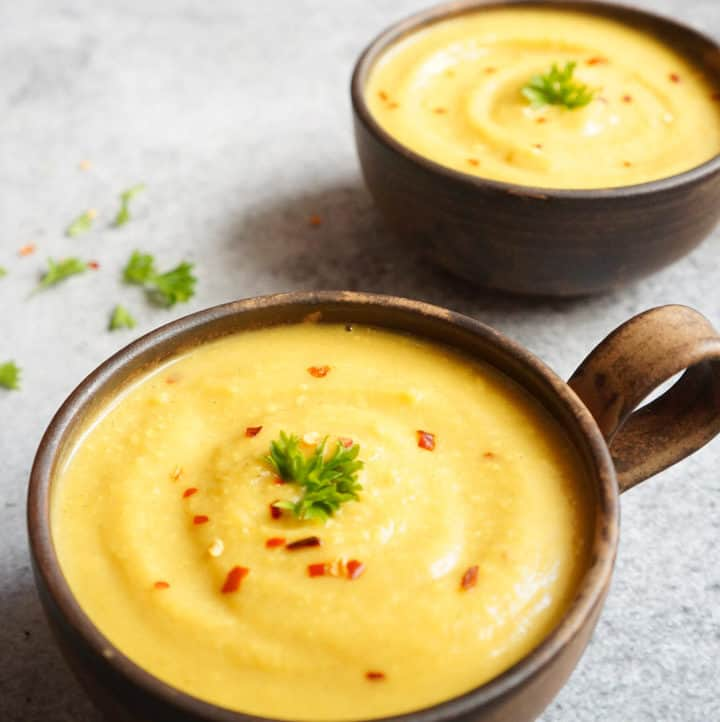 Turmeric Cauliflower Soup made in the instant pot in 2 serving bowls garnished with red chili flakes and parsley