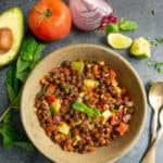Kala Chana Chaat. Black Chickpea Salad in a bowl with avocado, tomato, onion, mint and lime pieces