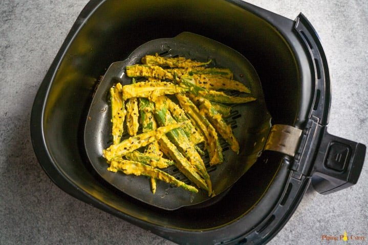 Slides okra covered in batter spread in air fryer grill pan