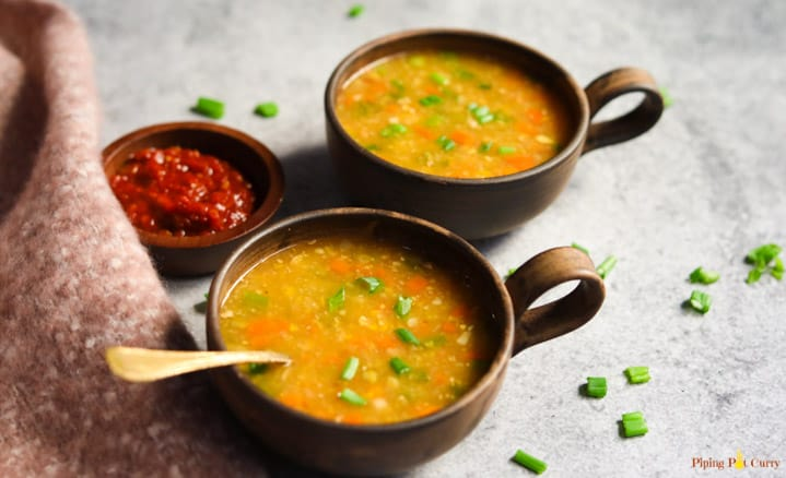 Two bowls of Sweet Corn Soup made in the Instant Pot along with chili sauce on the side.