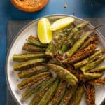 Bharwa Bhindi (Stuffed Okra) served in a plate with lemon wedges and the stuffed spices on the side.
