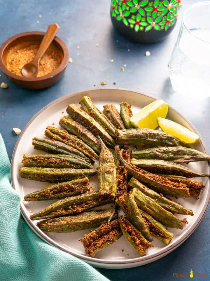 Bharwan Bhindi (Stuffed Okra) served in a plate with lemon wedges and the stuffed spices on the side.