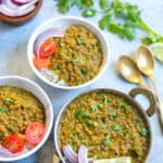 Masoor Dal made in instant pot served over rice in two bowls along with onions, tomato and rice