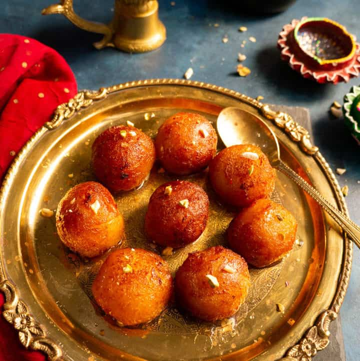 Gulab Jamun's served in a plate with some diya in the back for decoration