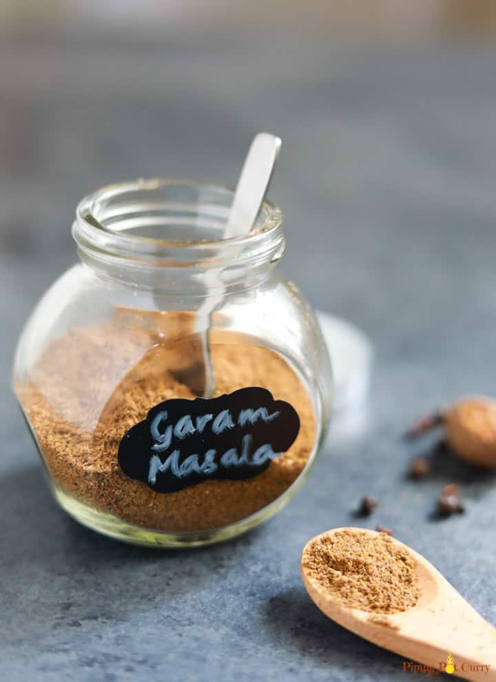 Homemade Garam Masala powder in a glass bottle with a spoon