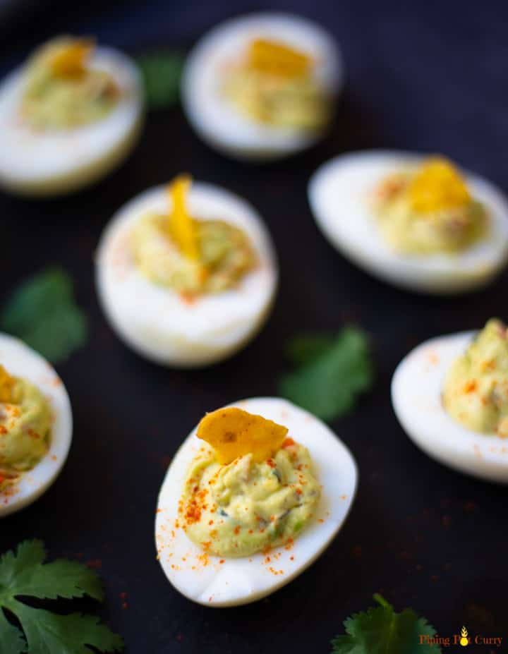 Guacamole Deviled Eggs on a black platter garnished with paprika and a tortilla chip