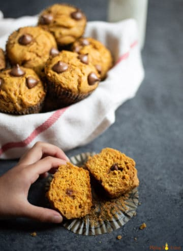Healthy Whole Wheat Carrot Muffin cut into two pieces being picked up, along with a basket of muffins.