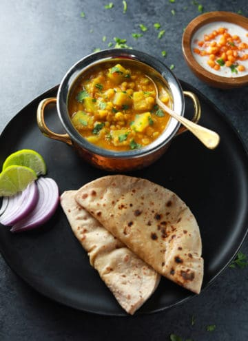 Lauki Chana Dal served in a black plate with roti, onions and lime.